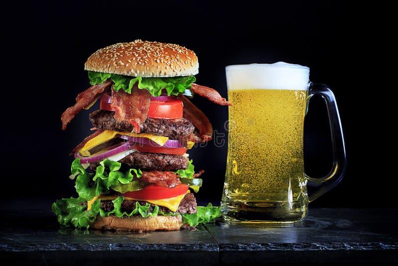 Hoher Speck-Cheeseburger und Bier stockfotos