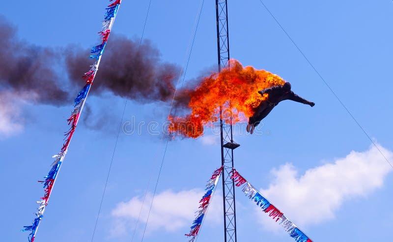 Hoher Taucher, der ein Feuertauchen weg von einer Plattform über einem Pool an einer angemessenen Show des Zirkusses durchführt lizenzfreie stockbilder