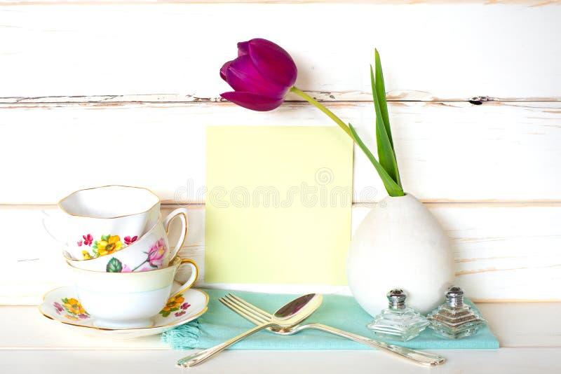 Hoher Tee-Zeit mit Stapel bunten Teetassen, purpurrote Tulpe im Vase, Gabel und Löffel, mit hellgrüner Menükarte auf weißem hölze lizenzfreie stockfotografie