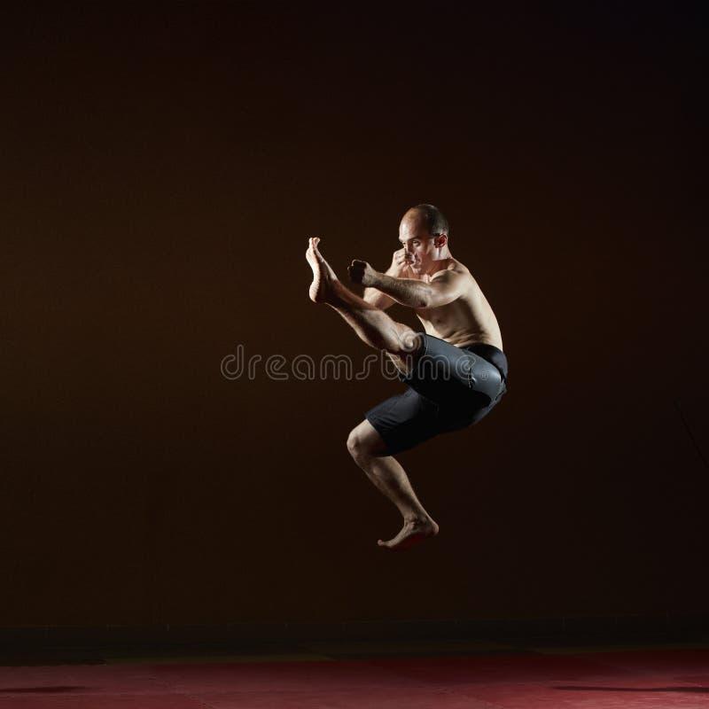 Hoher Tritt, den der Athlet in einem Sprung schlägt stockbild