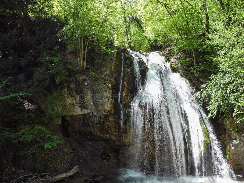 Hoher Wasserfall von einem Gebirgsfluss im grünen Frühlingswald lizenzfreie stockfotografie