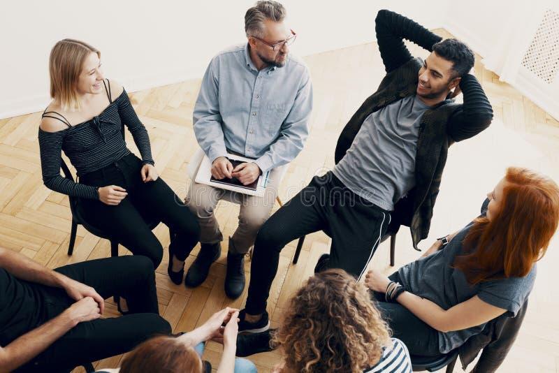 Hoher Winkel des spanischen Jugendlichen sprechend mit einem Therapeuten während des mee stockbilder