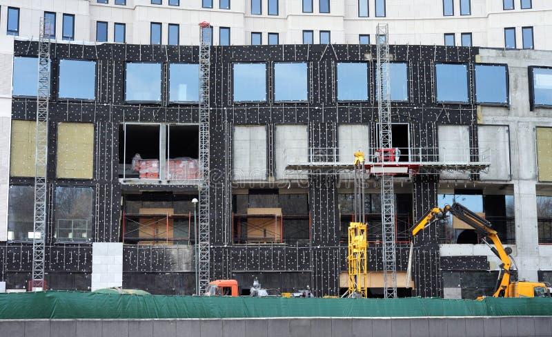 Hohes Gebäude im Bau mit einer Imprägnierung und einer Erwärmung von Wänden stockbilder