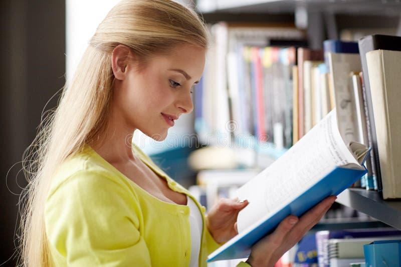 Hohes Schülermädchen-Lesebuch an der Bibliothek stockfoto