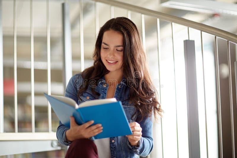Hohes Schülermädchen-Lesebuch an der Bibliothek lizenzfreie stockfotos
