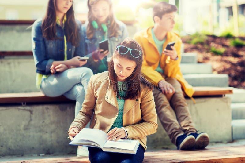 Hohes Schülermädchen-Lesebuch draußen stockbilder