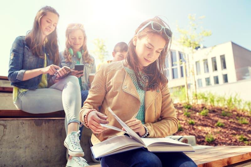 Hohes Schülermädchen-Lesebuch draußen stockfoto