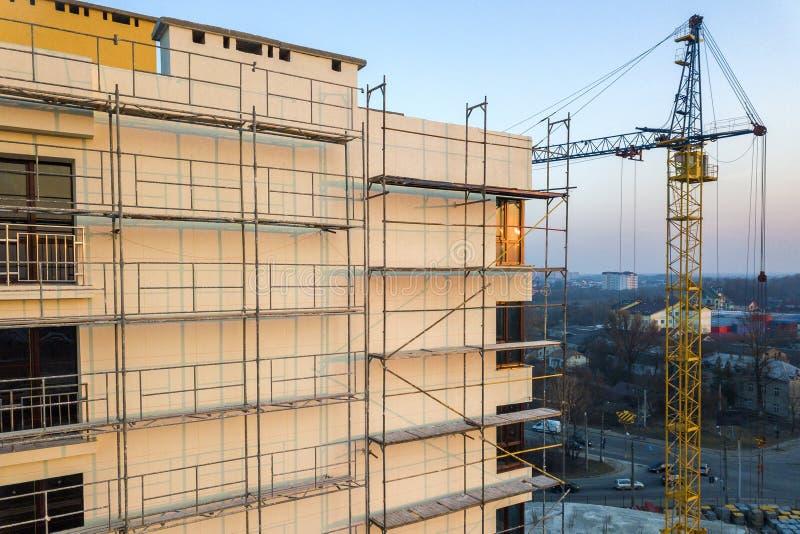 Hohes unfertiges Gebäude der Wohnung oder des Büros im Bau Backsteinmauer im Baugerüst, in den glänzenden Fenstern und im Turmkra lizenzfreies stockfoto