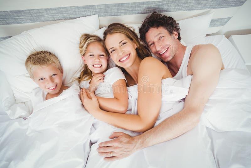 Hohes Winkelsichtporträt der glücklichen Familie entspannend auf Bett stockfoto