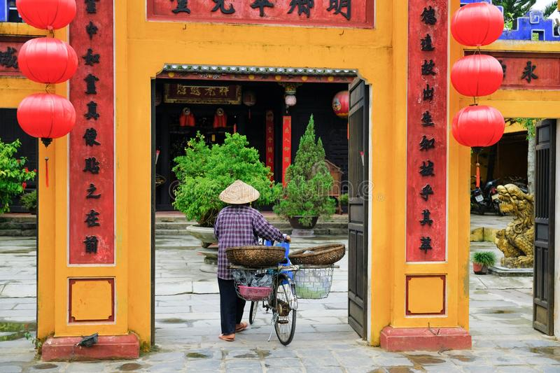 Hoi/Βιετνάμ, 11/11/2017: Τοπική βιετναμέζικη γυναίκα με το καπέλο ρυζιού και ποδήλατο που εισάγουν μια κίτρινη αίθουσα συνελεύσεω στοκ φωτογραφία με δικαίωμα ελεύθερης χρήσης