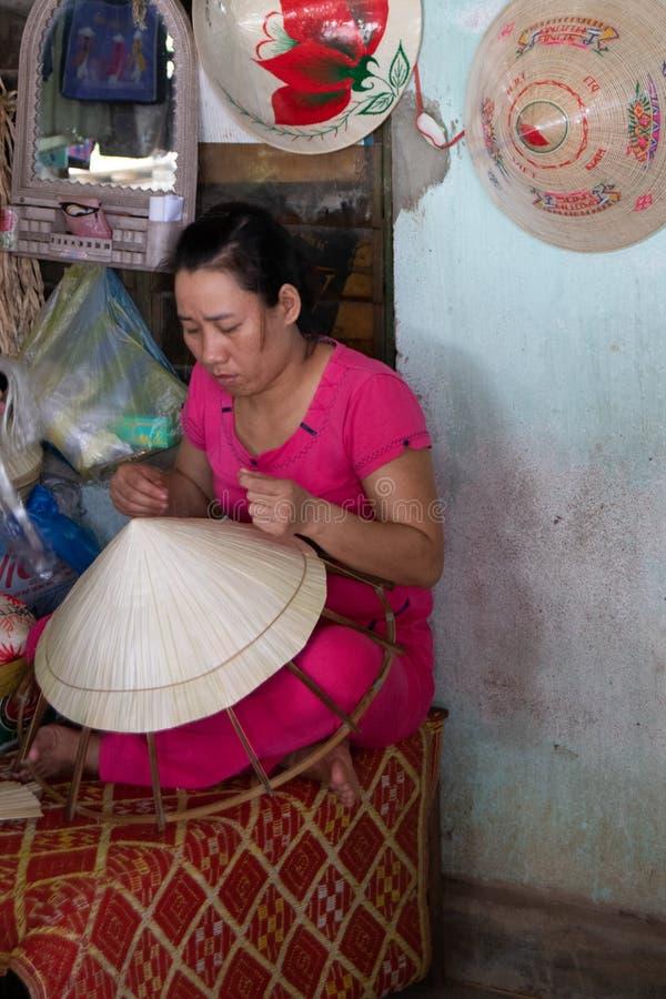 Hoi, Вьетнам, 30-ое октября 2016: Женщина в розовом костюме делая традиционную шляпу Вьетнама стоковое изображение