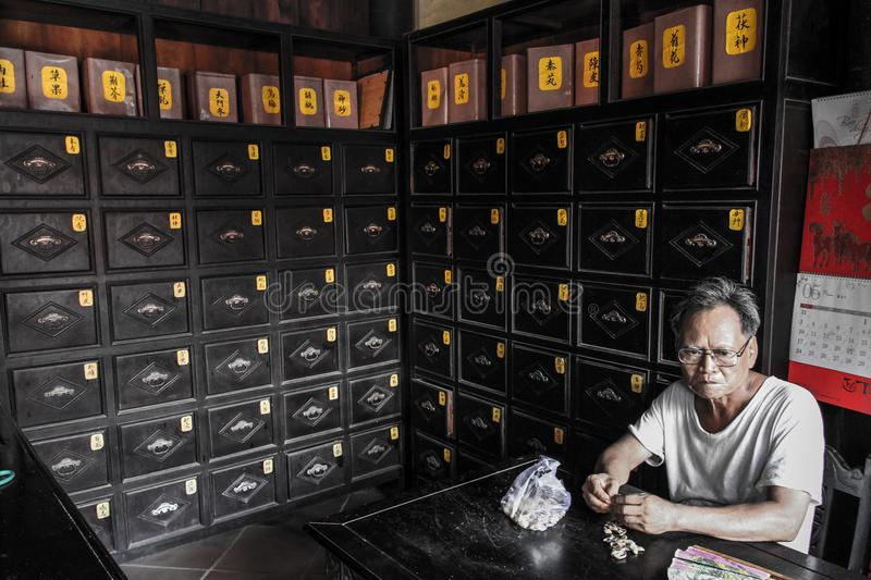 Old man eating peanuts in an old pharmacy, Hoi An, Quảng Nam Province, Vietnam. Hoi An formerly known as Fai-Fo or Faifoo, is a city with a population of royalty free stock photos