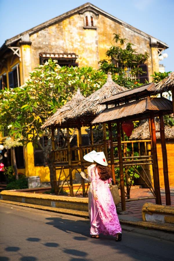 HOI, QUANG NAM, VIETNAM, le 26 avril 2018 : Femmes vietnamiennes portant ao Dai Vue de rue avec de vieilles maisons en ville anti images libres de droits