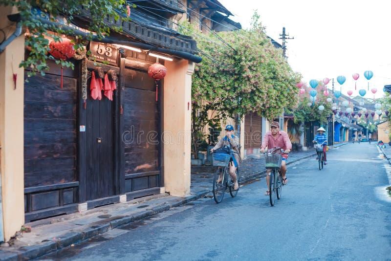 HOI, QUANG NAM, VIETNAME, O 20 DE SETEMBRO DE 2018: Povos de Vietname, bicicleta vietnamiana do passeio sobre durante o nascer do fotos de stock royalty free