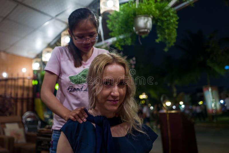 Hoi An, Vietnam - April 19, 2018: Caucasian girl enjoys neck massage in Hoi An. Hoi An, Vietnam - April 19, 2018: Caucasian girl enjoys neck massage in Hoi An stock photography