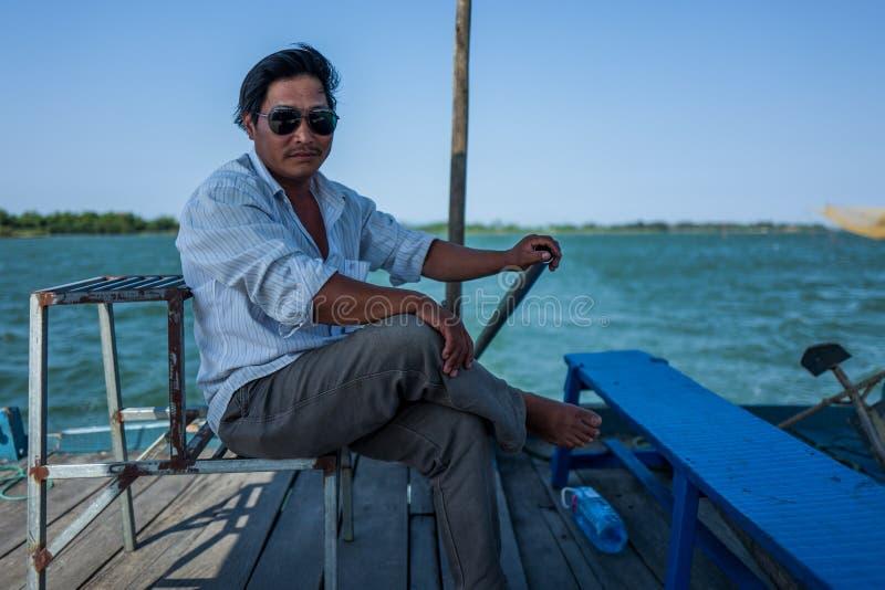 Hoi An, Vietnam - April 21, 2018: De Vietnamese kapitein van lokale boot stuurt boot en bekijkt camera stock fotografie