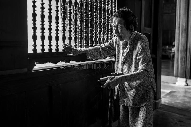 Hoi An, Vietnam - April 20, 2018: Elderly woman slowly walks old house in Hoi An old city. royalty free stock photography