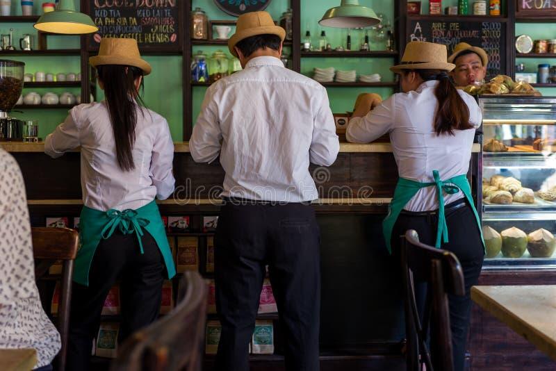 Hoi An Vietnam - April 20, 2018: Uppassaren och servitriers kontrollerar en beställning på en stång i Hoi An fotografering för bildbyråer
