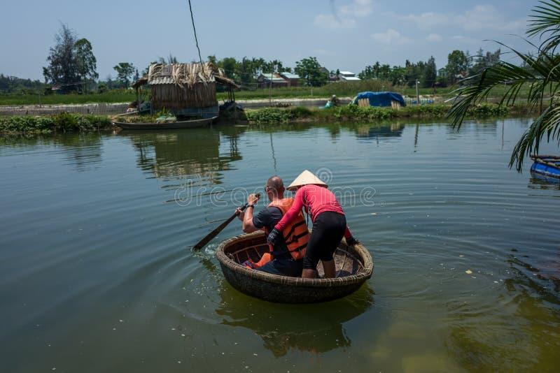 Hoi An, Vietnam - 21 aprile 2018: L'uomo caucasico impara utilizzare la barca rotonda di Thung Chai con la guida in Hoi An fotografia stock libera da diritti