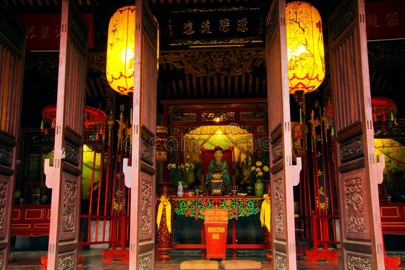 View beyond open doors and bright yellow chinese lanterns into Buddhist colorful temple stock image
