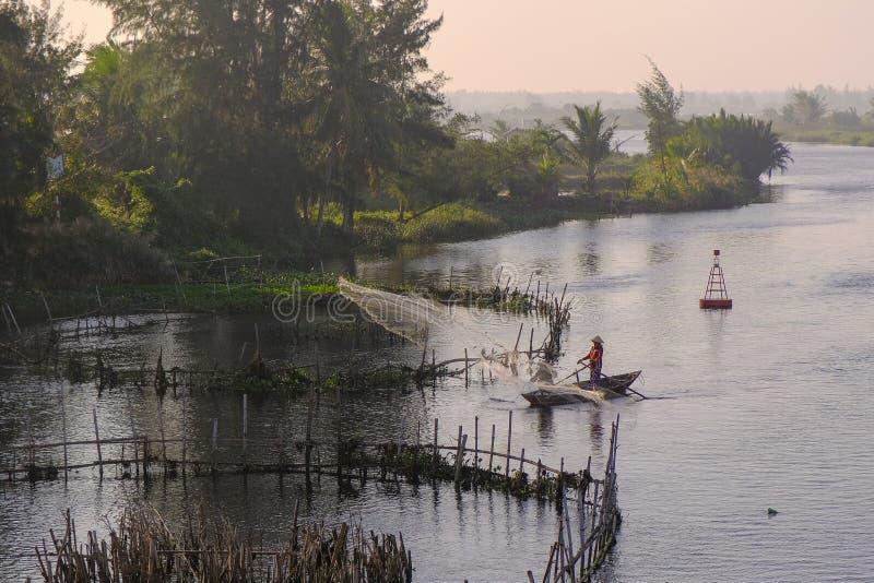 Hoi An/Vietnam, 12/11/2017: Een traditionele boot met lokale Vietnamese vissers die een net werpen in een rivier in Hoi An, Vietn royalty-vrije stock afbeelding
