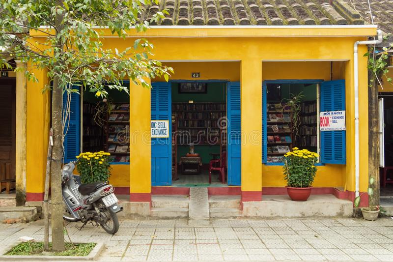 Yellow house with blue doors and windows and flower pots with yellow chrysanthemums and motorbike next to it. Small book shop. stock photography