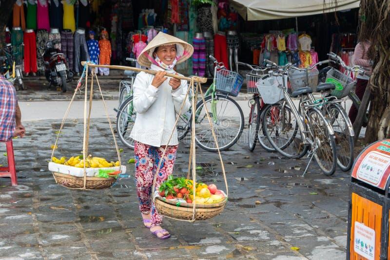 Hoi, Vietnam, il 30 ottobre 2016: Venditori ambulanti sorridenti della donna che vendono gli ortaggi freschi immagini stock