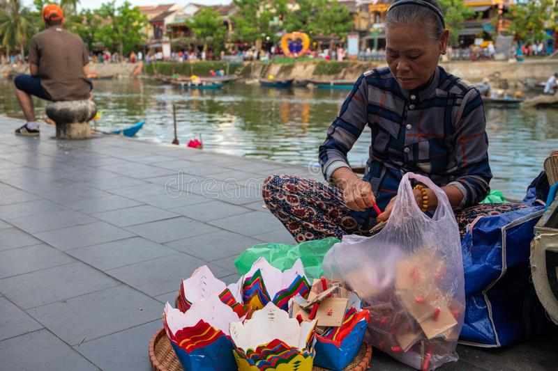 Hoi An, Vietnam - 28 Jul 2019: Old woman making floating candles. Vietnamese people portrait. South Asia travel photo royalty free stock images
