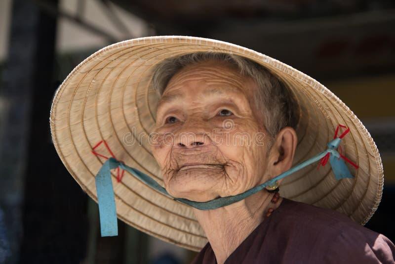 Hoi An VIETNAM, Juli 2017: Stående av den äldre kvinnan som bär den koniska hatten royaltyfri bild