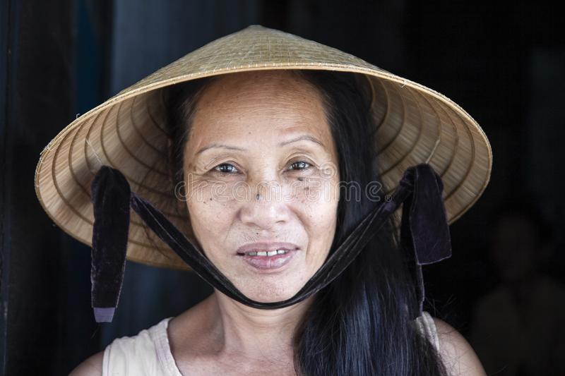 Hoi An, VIETNAM, July 2017 : closeup face portrait of vietnam woman wearing conical hat royalty free stock photos