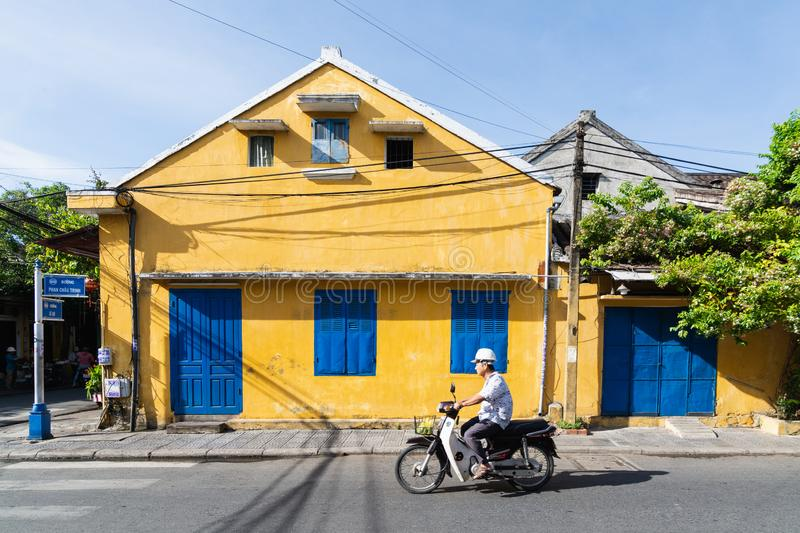Hoi An, Vietnam - June 2019: man riding scooter next to colorful house in old town royalty free stock images
