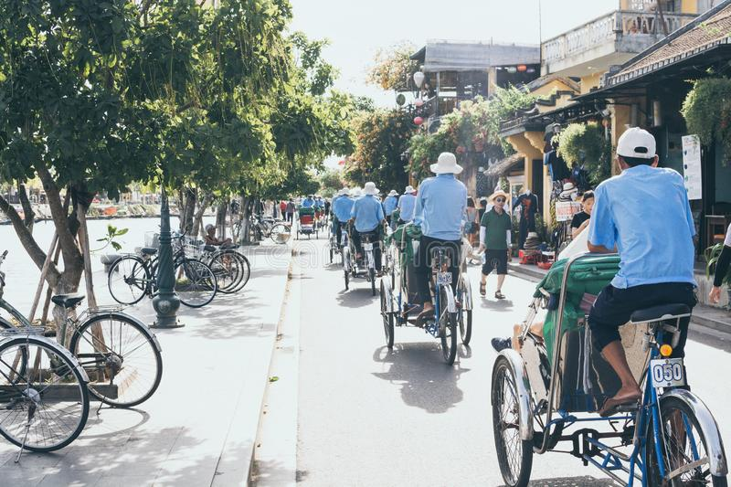 Hoi An, Vietnam - June 2019: rickshaws transporting tourists in the historic town center. Hoi An, Vietnam - June 2019: bicycle rickshaws transporting tourists in royalty free stock images