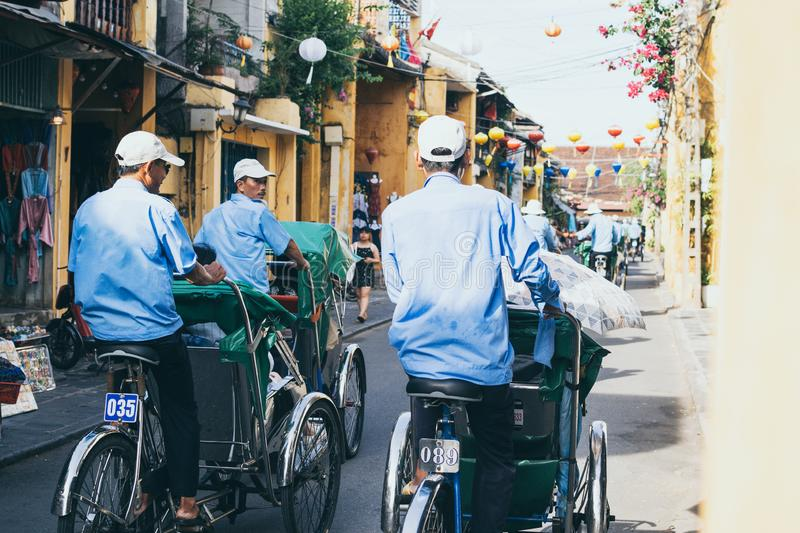 Hoi An, Vietnam - June 2019: rickshaws transporting tourists in the historic town center. Hoi An, Vietnam - June 2019: bicycle rickshaws transporting tourists in stock images