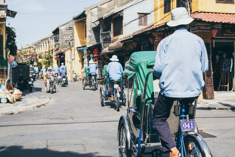 Hoi An, Vietnam - June 2019: rickshaws transporting tourists in the historic town center. Hoi An, Vietnam - June 2019: bicycle rickshaws transporting tourists in royalty free stock photography