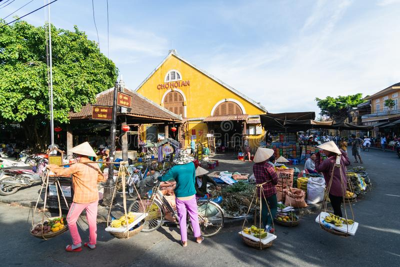 Hoi An, Vietnam - June 2019: street fruit vendors walking by colorful market building in old town stock images