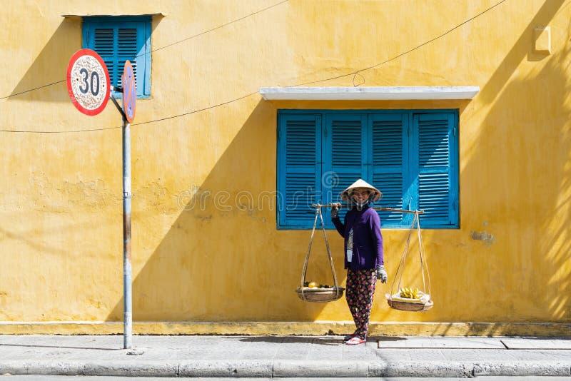 Hoi An, Vietnam - Juni 2019: de verkopersvrouw die van het straatfruit door kleurrijk huis in oude stad lopen stock foto