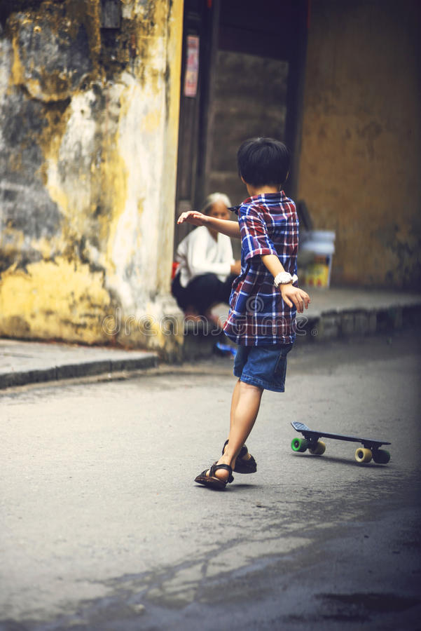 HOI, VIETNAM, AM 15. JUNI: Ein Kind, das in die Straße, an Skateboard fährt lizenzfreie stockfotos