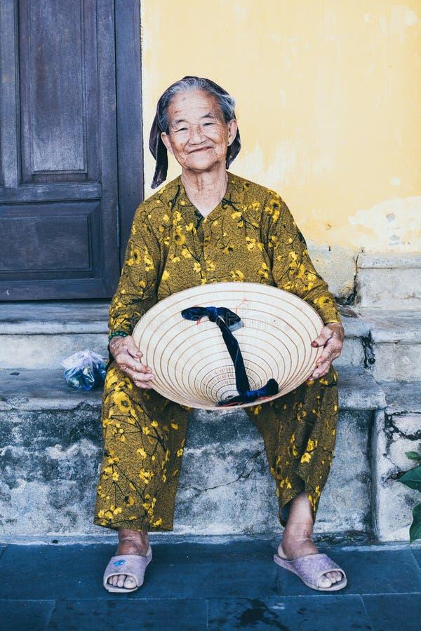 Hoi An Vietnam - Juni 2019: gammal vietnamesisk kvinna med den koniska hatten royaltyfria bilder