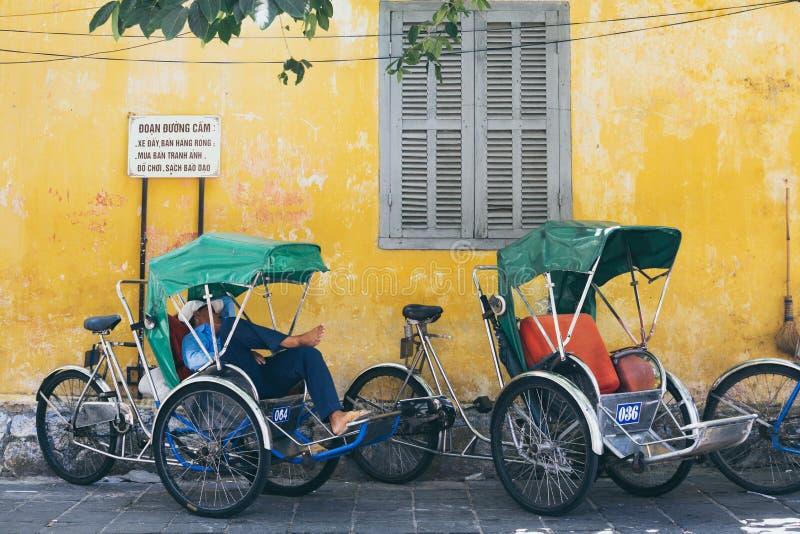 Hoi An Vietnam - Juni 2019: Vietnamesisk rickshaw som sover i cykelvagn royaltyfri fotografi