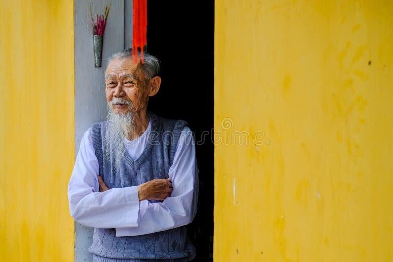 Hoi An/Vietnam, 12/11/2017: Klok gammal vietnamesisk man som ler och välkomnar folk till hans hus med gula väggar i Hoi An, royaltyfri bild
