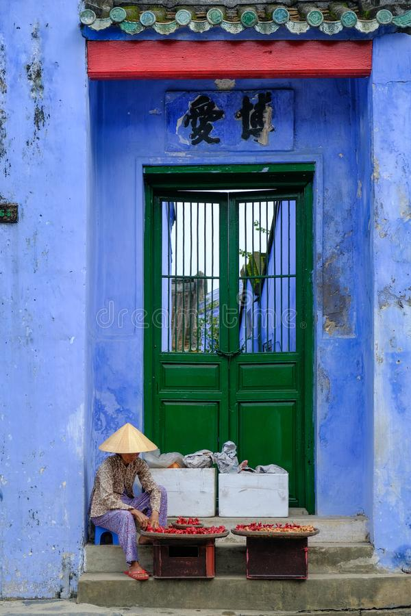 Hoi An / Vietnam, 12/11/2017: Local Vietnamese woman sitting in front of a traditional house entrance with blue walls and selling stock images
