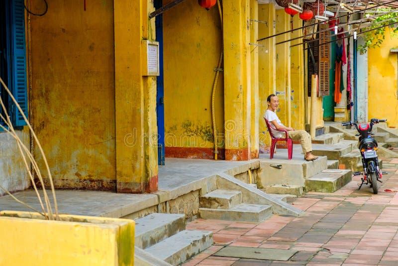 Hoi An/Vietnam, 12/11/2017: Lokale Vietnamese mensenzitting voor traditionele huizen met sier gele muren in Hoi An, royalty-vrije stock foto's