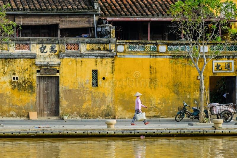 Hoi An/Vietnam, 12/11/2017: Lokale Vietnamese vrouw die met rijsthoed voor traditionele huizen met sier geel lopen stock afbeeldingen
