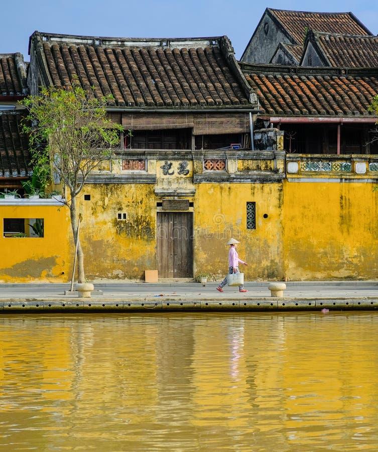 Hoi An/Vietnam, 12/11/2017: Lokale Vietnamese vrouw die met rijsthoed voor traditionele huizen met sier geel lopen royalty-vrije stock foto's