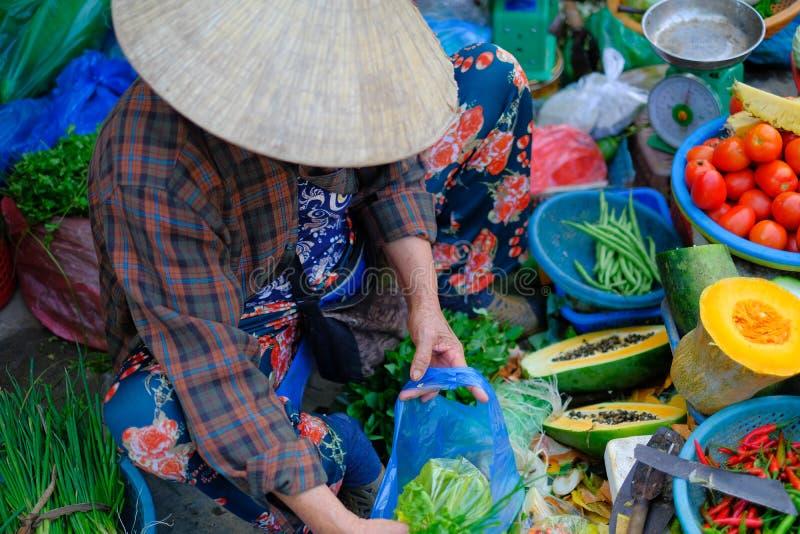Hoi An/Vietnam, 12/11/2017: Lokale Vietnamese vrouw met de verkopende groenten van de rijsthoed op een traditionele straatmarkt i royalty-vrije stock fotografie