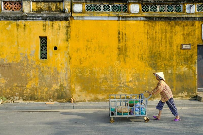 Hoi An/Vietnam, 12/11/2017: Lokale Vietnamese vrouw met rijsthoed die een vervoer voor traditionele huizen duwen met royalty-vrije stock foto's