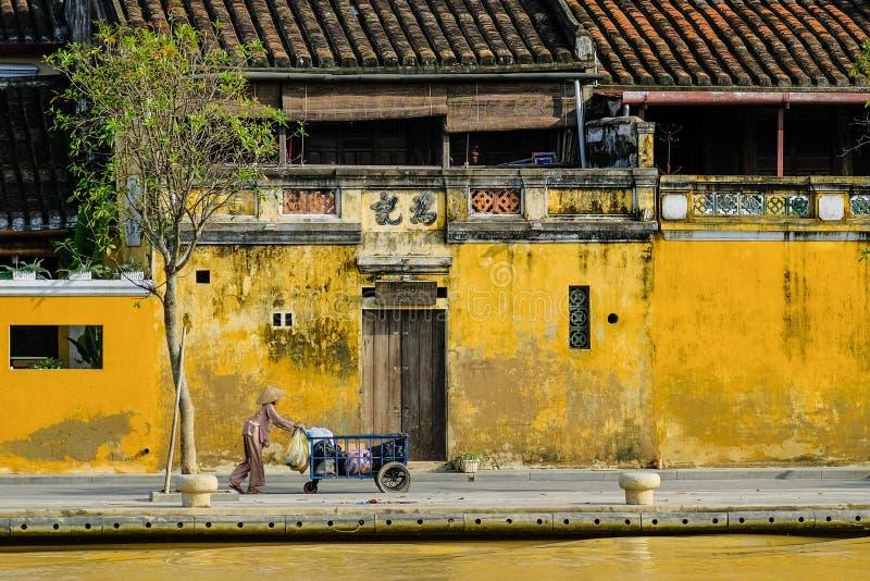 Hoi An/Vietnam, 12/11/2017: Lokale Vietnamese vrouw met rijsthoed die een vervoer voor traditionele huizen duwen met royalty-vrije stock afbeeldingen