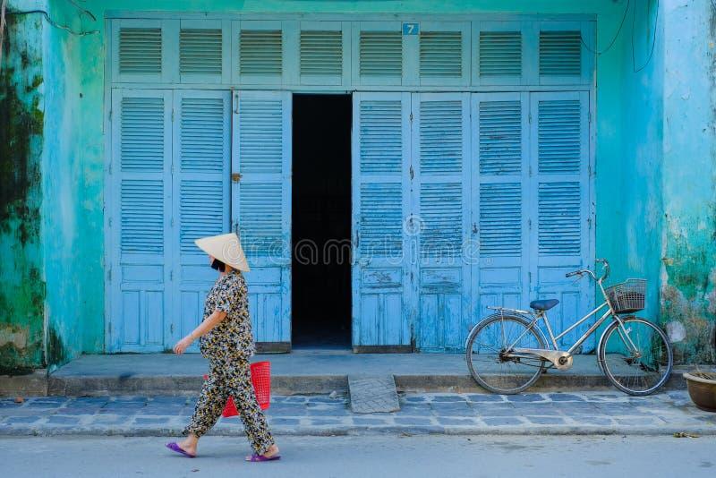 Hoi An/Vietnam, 12/11/2017: Lokale Vietnamese vrouw met rijsthoed die naast een fiets voor een traditioneel huisblauw overgaan stock afbeelding