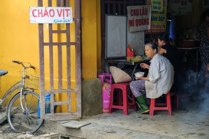 Hoi An/Vietnam, 11/11/2017: Lokale Vietnamese vrouw met rijsthoed en fiets die in een box van het straatvoedsel in Hoi An in Viet stock fotografie