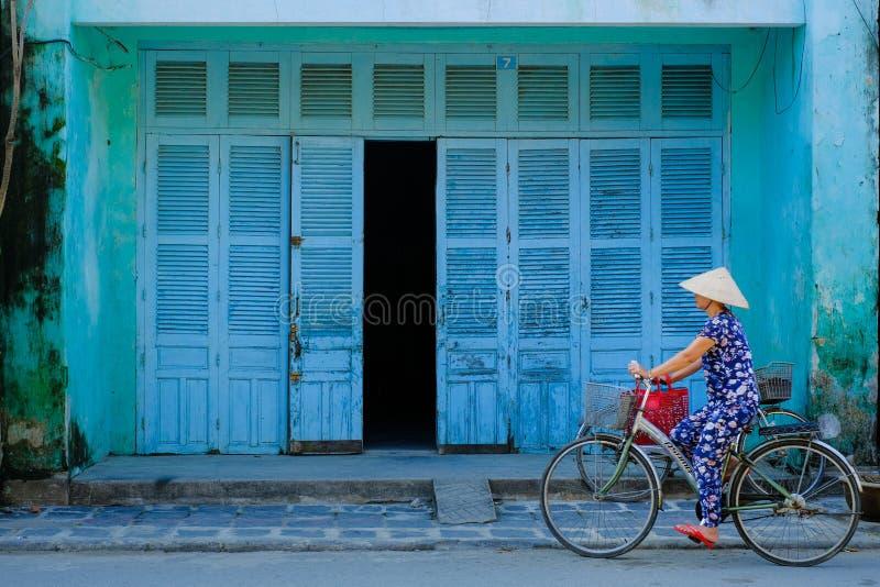 Hoi An/Vietnam, 12/11/2017: Lokale Vietnamese vrouw met rijsthoed op een fiets die voor een traditionele huis blauwe muren overga stock afbeelding